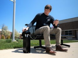 Man sitting on a bench by a park charging a phone connected to a black electrical power pedestal