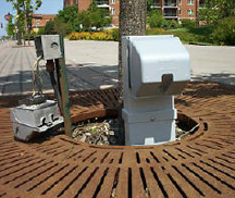 grey outdoor power pedestal installed by tree